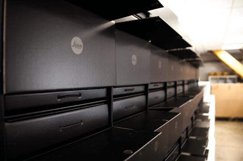 Stapel von schwarzen leicaboxen konfektionierte werbemittel, konfektionieren in handarbeit